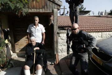 old man being wheeled out in a wheelchair from a house, an Israeli soldier nearby