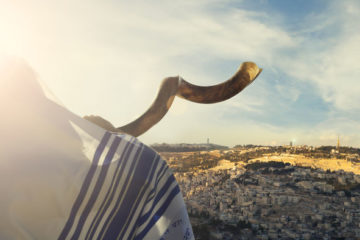 Shofar being blown overlooking a hill in israel