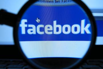 facebook logo through a magnifying glass