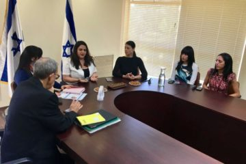 the victims sitting around a table at knesset meeting with someone