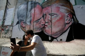 the mural with two people kissing in front of it
