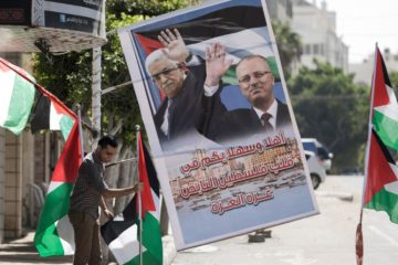 man setting up palestinian flags and supportive posters of reconciliation