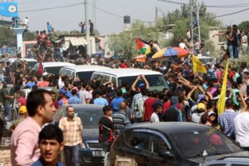 palestinians crowding around the vans of the west bank PM in gaza
