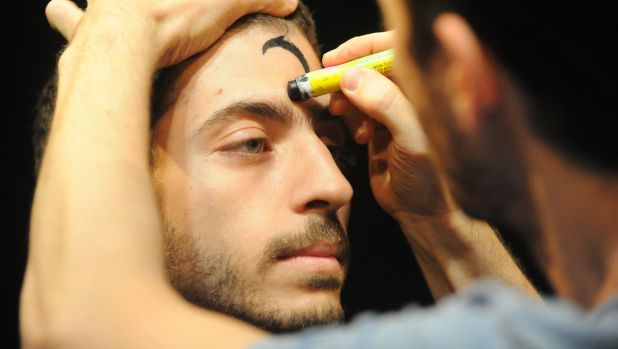 actor writing on another actor's forehead in a scene from the play