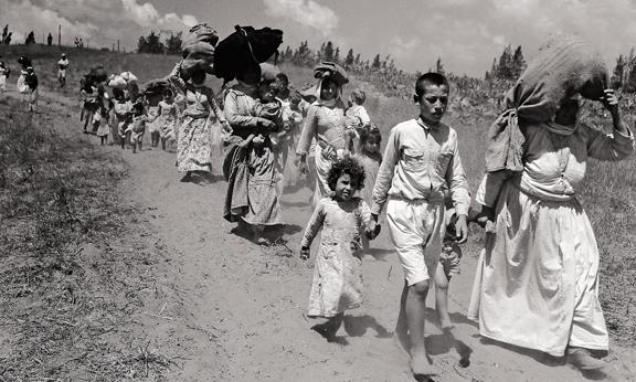 black and white photo of what appears to be refugees walking.