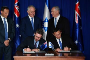 Prime Ministers Turnbull and Netanyahu standing behind others signing at a ceremony