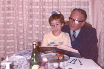 Bram as a young boy sitting on his grandfather's knee at the table