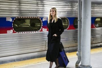 Ivanka Trump walking along a train platform pulling a suitcase