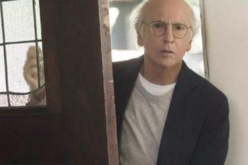 Larry David entering a door looking concerned