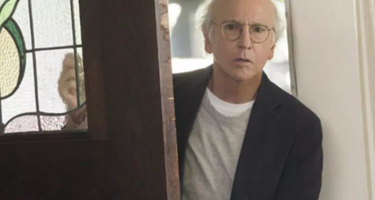 Larry David entering a door looking concerned