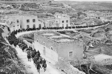 a line of light horse soldiers moving through a town in 1918.
