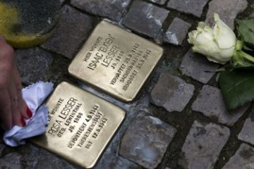 two memorial stones in the pavement, one being cleaned