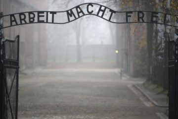 scary pic of the gates of auschwitz with the arbeit mach frei sign, with foggy background