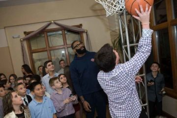 Kyle with group of kids and one child is about to shoot a basket
