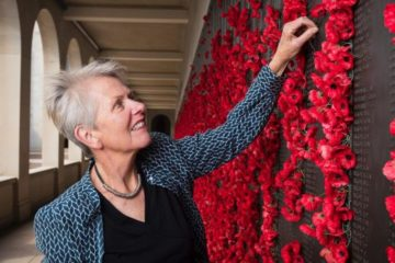 Judith with arm extended placing a flower in the wall that is filled with many poppies