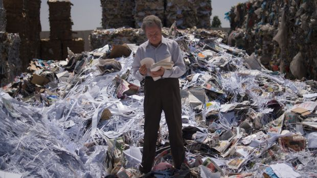 man flipping through papers standing on a mountain of rubbish/papers.