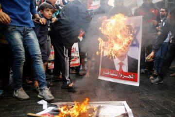 protestors burning posters of Trump