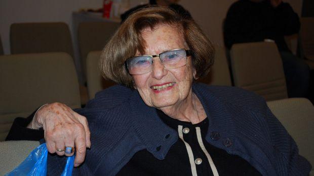 A smiling, elderly Kitia closeup, sitting in a theatre