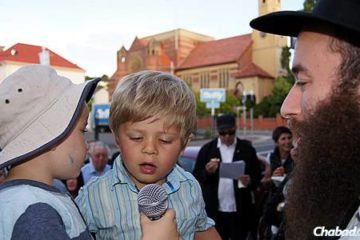 a rabbi interviewing two little kids with a microphone