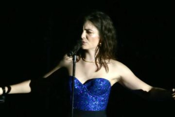 Lordeon stage in blue dress, arms spread, at the microphone