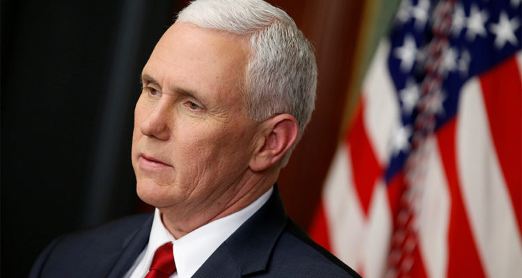 Headshot of Mike Pence, American flag behind, looking pensive into the distance