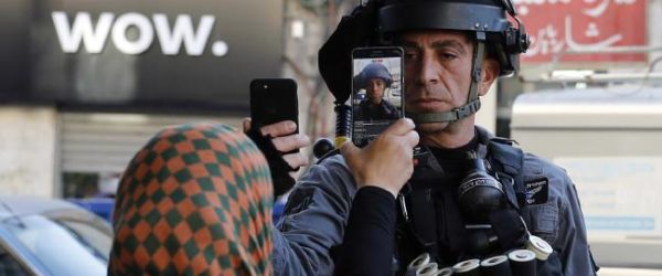 Israeli police officer taking a photo of a Palestinian woman, whilst she simultaneously photographs him.