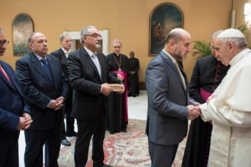 Pope in an office with people, shaking hands