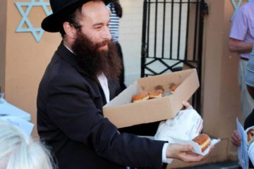 Rabbi Gordon with a tray of doughnuts handing them out
