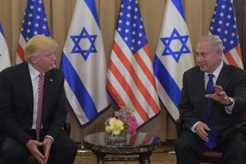 Presidents Trump and Netanyahu seated, talking in front of american and israeli flags