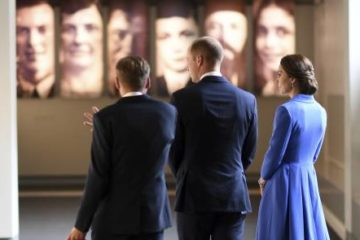 william and kate and other with backs to camera, looking at the holocaust exhibition