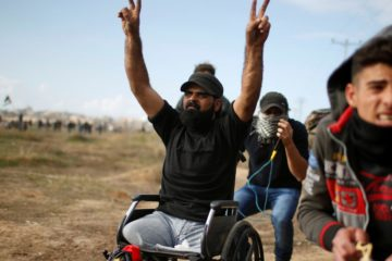 ibraheem in wheelchair making peace signs with both hands in the air