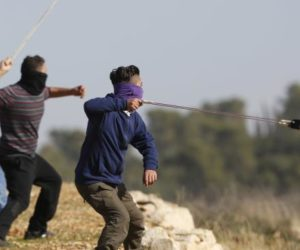 three masked protesters firing slingshots