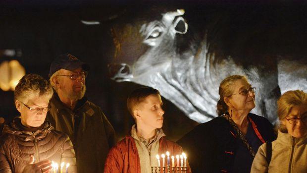 some people standing in the dark outside, boy holding hanukkiah