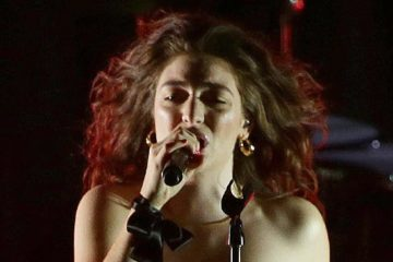 Lorde close up, singing on stage into microphone