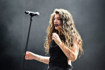 Lorde on stage near a microphone