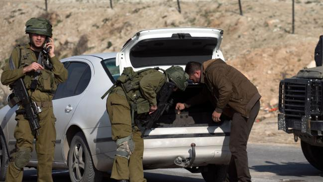 two soldiers checking the boot of a car at a checkpoint