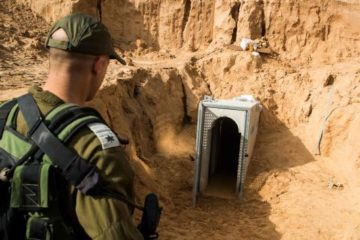 Israeli soldier in the foreground looking at a tunnel entrance