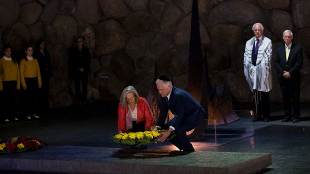 Prime Minister Turnbull and wife both bending down to lay wreath at yad vashe